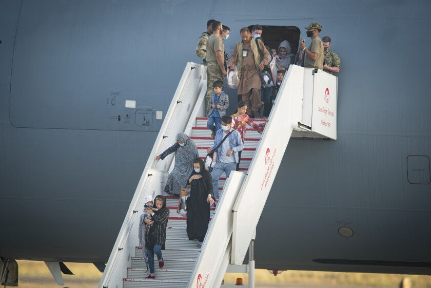Evacuees from Afghanistan disembark from a U.S. airforce plane at the Naval Station in Rota, southern Spain.