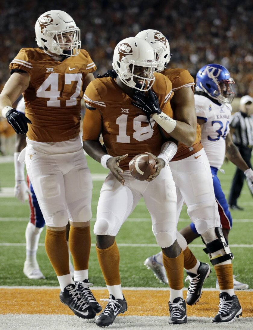 Texas quarterback Tyrone Swoopes (18) celebrates with teammates Andrew Beck (47) and Caleb Bluiett, right, after he scored a touchdown against Kansas during the first half of an NCAA college football game, Saturday, Nov. 7, 2015, in Austin, Texas. (AP Photo/Eric Gay)