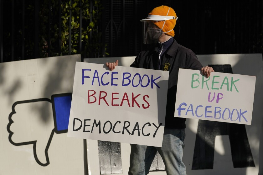 A demonstrator is outside the home of Facebook CEO Mark Zuckerberg in November 2020.