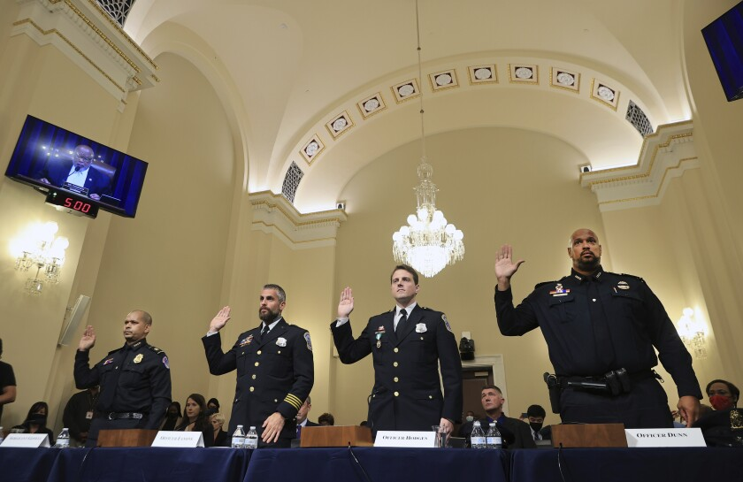 Police officers in uniform, rights hands raised in congressional hearing room