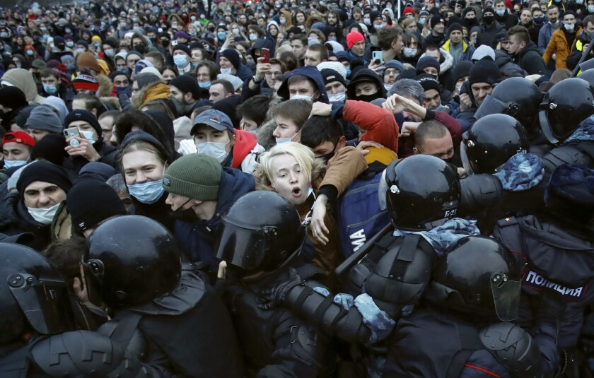 Police in riot gear and dark face shields push against a dense crowd of protesters, many in face masks.