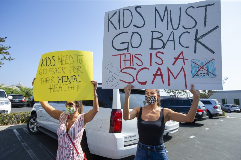 Women protesting remote learning hold signs saying Kids must go back, This is a scam