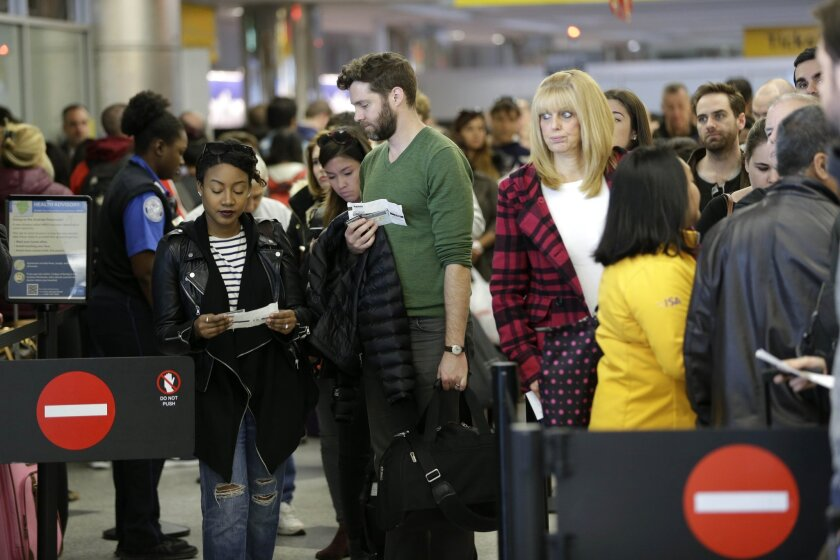 Passengers wait in line to clear security at LaGuardia Airport in New York.