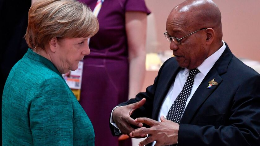 German Chancellor Angela Merkel talks with South African President Jacob Zuma at the Group of 20 Sum
