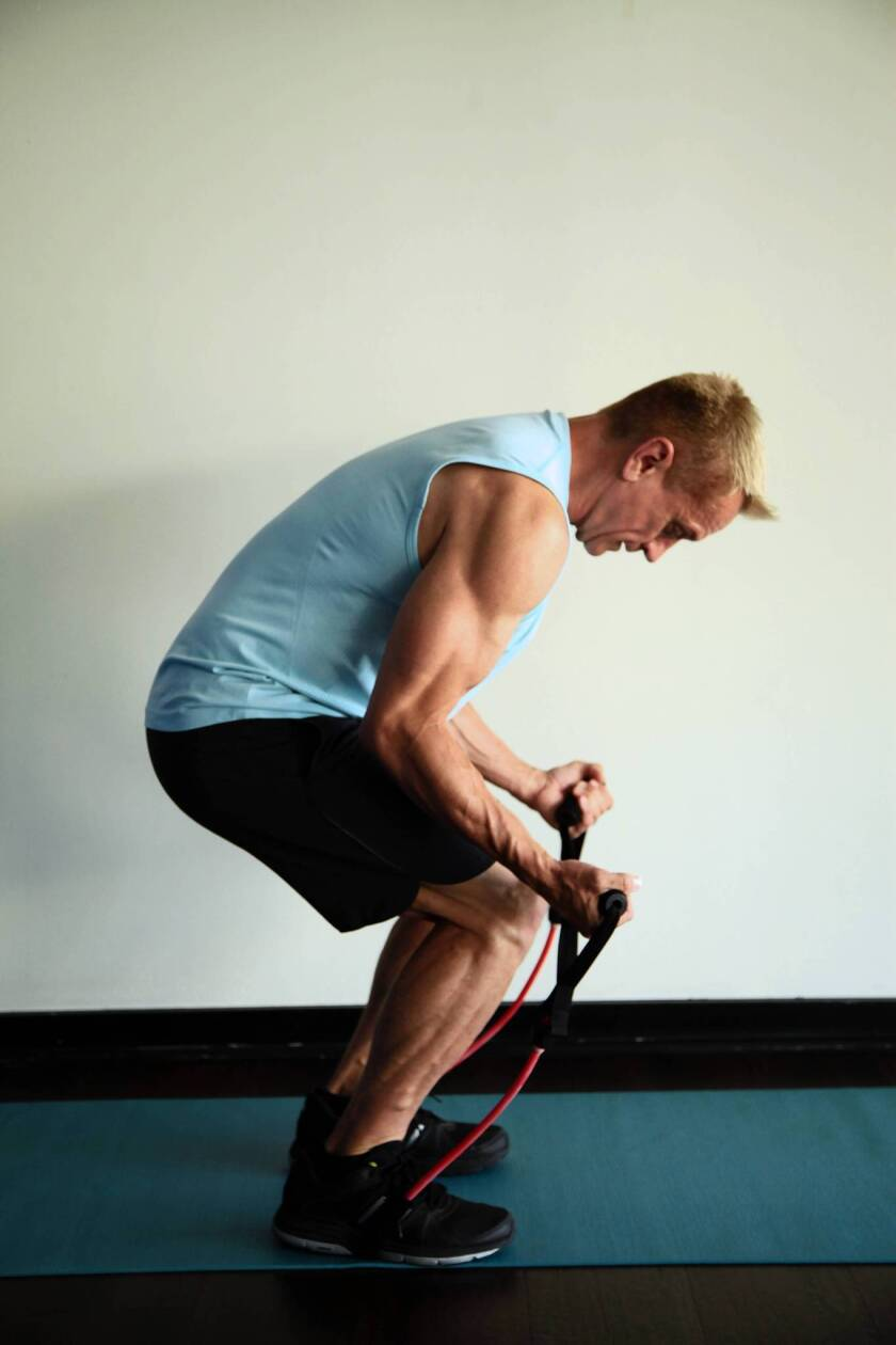 John Garey demonstrates the middle portion of the Crouch to Superman exercise, which uses a stretch band.