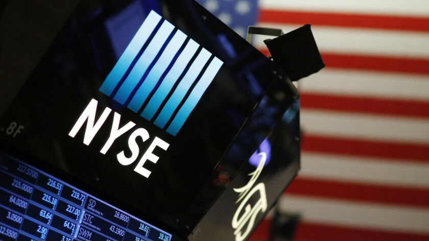 A New York Stock Exchange display hovers above the trading floor.