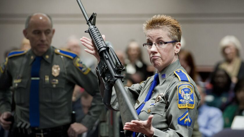 Conn. State Police Det. Barbara J. Mattson with a Bushmaster AR-15 rifle, the same make and model used in the 2012 Sandy Hook School massacre.