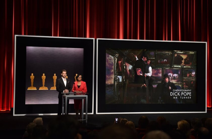 Chris Pine and Academy President Cheryl Boone Isaacs announce Dick Pope as a nominee for best cinematography in the film 'Mr. Turner' during the presentation of the Academy Awards nominations on Jan. 15.