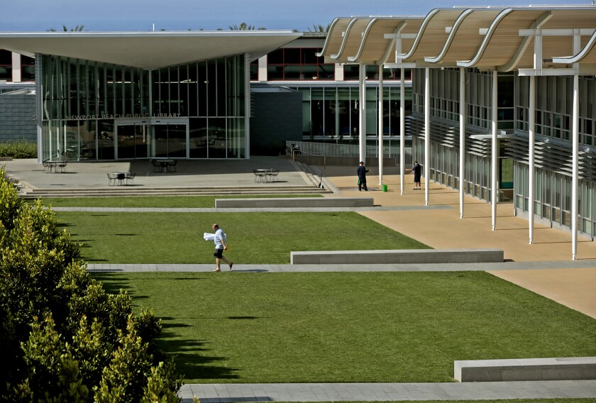 A pedestrian walks past the lawns between Newport Beach City Hall and the public library.