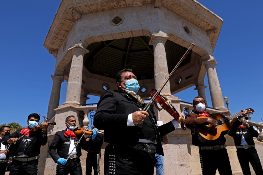 Israel Moreno, center, and Jose Cervantes, right, along with other mariachi musicians.