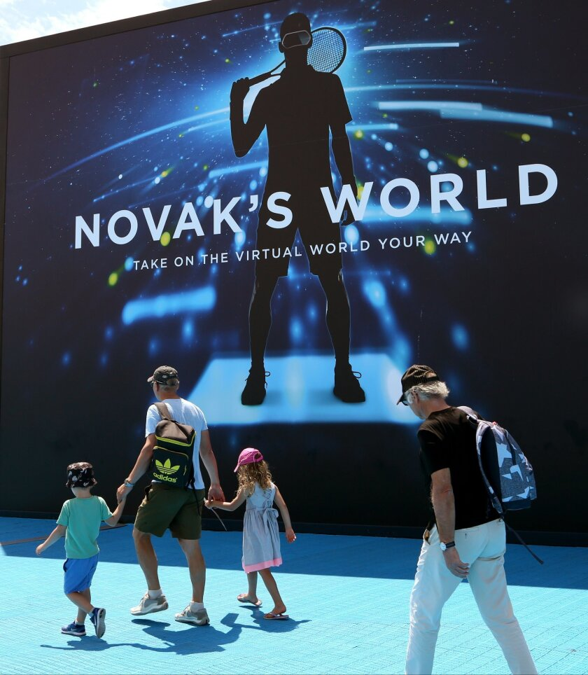 """Spectators walk past a large billboard showing defending champion Serbia's Novak Djokovic at the Australian Open tennis championships in Melbourne, Australia, Wednesday, Jan. 27, 2016. His face smiles at fans from sponsor's billboards. His voice gives inspirational advice over center-court speakers between matches. There's even a new addition to Melbourne Park called """"Novak's World,"""" where fans can slip on virtual reality goggles and feel as if they're walking in Djokovic's shoes — as he stretches in the locker room and then walks out onto the court as the crowd roars. (AP Photo/Jocelyn Gecker)"""