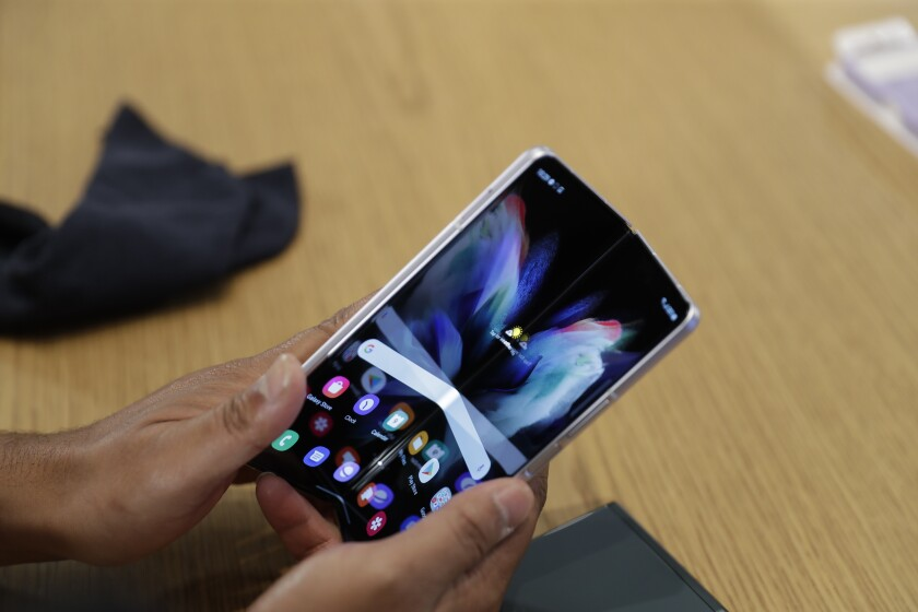 A person demonstrates folding the Samsung Galaxy Fold 3 on Monday, Aug. 9, 2021 at Samsung KX in London. Samsung is hoping cheaper but more durable versions of its foldable phones will broaden the appeal of a high-concept design that's so far fizzled with consumers. (AP Photo/Tristan Werkmeister)