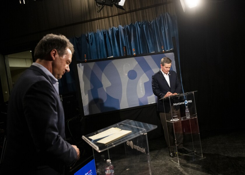 FILE - In this Sept. 28, 2020, file photo, Gov. Steve Bullock, left, and U.S. Sen. Steve Daines, R-Mont., prepare their notes before the beginning of their televised debate at the KUFM-TV studio at the University of Montana in Missoula, Mont. Political groups fighting for control of the U.S. Senate have poured more than $118 million into the contest between Bullock and Daines. For Montana residents, it means an unrelenting barrage of advertisements any time they turn on their computers, televisions and radios or open their mailboxes. (Ben Allan Smith/The Missoulian via AP, File)