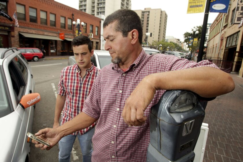 Sidecar driver Angelo Filippatos, right, and rider Harry Birnbaum look at the ridesharing company's app in downtown San Diego. The app connects people who need rides with those willing to drive.| Photo by Hayne Palmour IV U-T San Diego