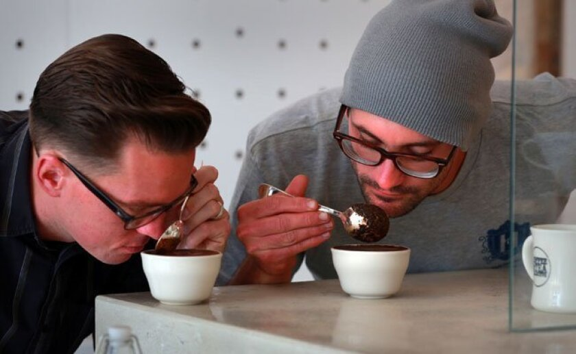 Wil Ryland, left, a customer at Coffee and Tea Collective, follows instructions from owner Daniel Holcomb in sampling different coffees at the tasting bar.