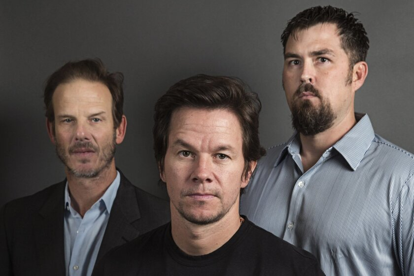 "This Dec. 5, 2013 photo shows director Peter Berg, from left, actor Mark Wahlberg and former Navy SEAL Marcus Luttrell in New York. In the age of the superhero, the movies' most reliable real-life hero has been the Navy SEAL. ""Lone Survivor,"" starring Mark Wahlberg, is the latest in a string of fil"