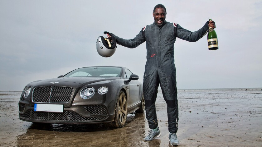 """Idris Elba with the Bentley Continental GT Speed he used to break a long-standing speed record at Pendine Sands in Wales. The feat is part of Discovery's upcoming, four-part show """"Idris Elba: No Limits."""""""