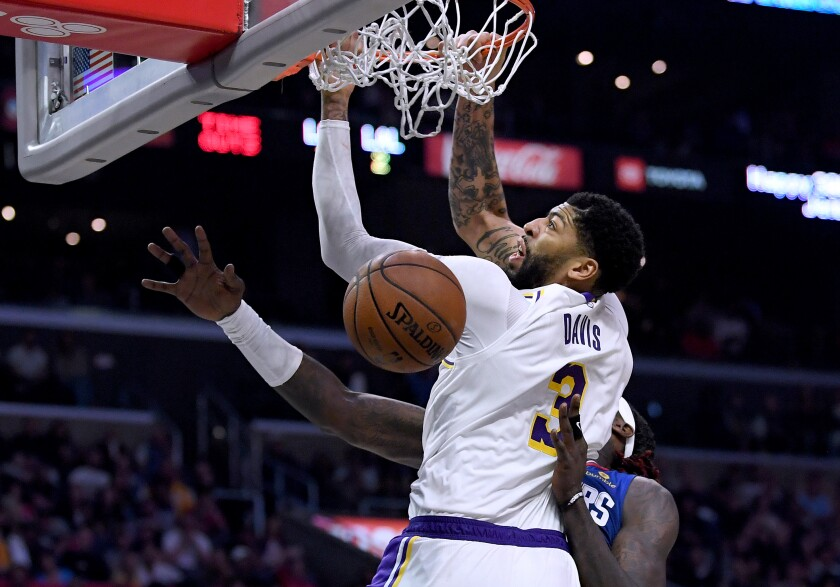 Lakers forward Anthony Davis dunks over Clippers forward Montrezl Harrell during the Lakers' 112-103 win Sunday at Staples Center.