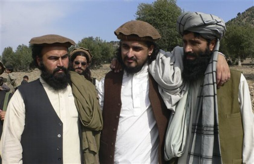 In this image taken on Oct. 4, 2009, Pakistan's new Taliban leader Hakimullah Mehsud, center, stands pose with his deputy Waliur Rehman, left, and spokesman Azam Tariq in Sararogha in Pakistani tribal area of South Waziristan along Afghanistan border. Pakistan blamed Taliban militants Tuesday for the deadly suicide bombing at the U.N. food agency's heavily fortified compound in the capital as authorities detained some of the guards posted outside to try to determine how the attacker gained entry.(AP Photo/Ishtiaq Mahsud)