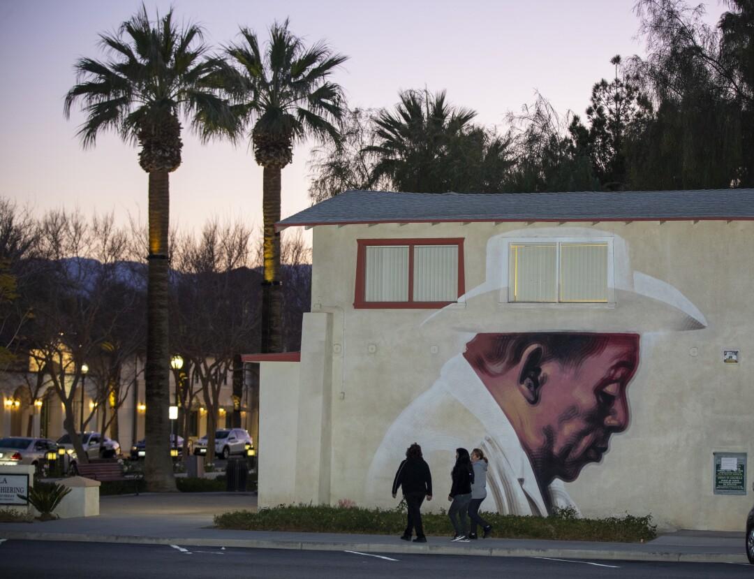 Pedestrians pass a mural in downtown Coachella.