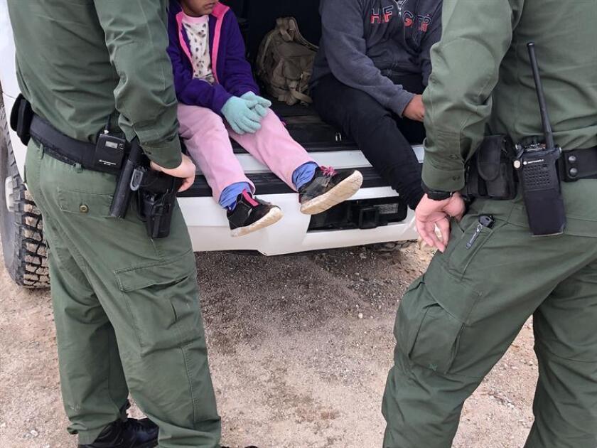 Fotografía donde aparecen dos agentes de la Patrulla Fronteriza mientras atienden a unos niños en un punto del área conocido como Quitobaquito, en la frontera de Arizona con México (EE.UU.). EFE/Archivo