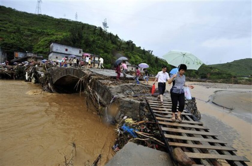 In this photo released by China's Xinhua News Agency, people walk across a flood-damaged bridge in Qianpai Town in Xinyi, south China's Guangdong Province, Wednesday, Sept. 22, 2010. Typhoon Fanapi swamped Guangdong province after making a direct hit on the island of Taiwan on Sunday. (AP Photo/Xin