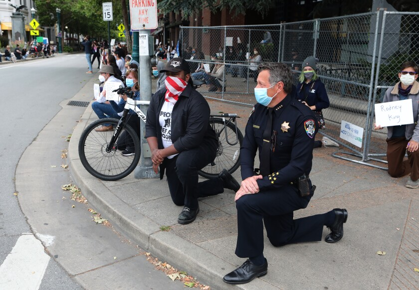 Santa Cruz Mayor Justin Cummings and Police Chief Andrew Mills take a knee along with hundreds gathered Saturday on Pacific Avenue in downtown Santa Cruz to honor the memory of George Floyd and bring attention to institutionalized police violence against black people.