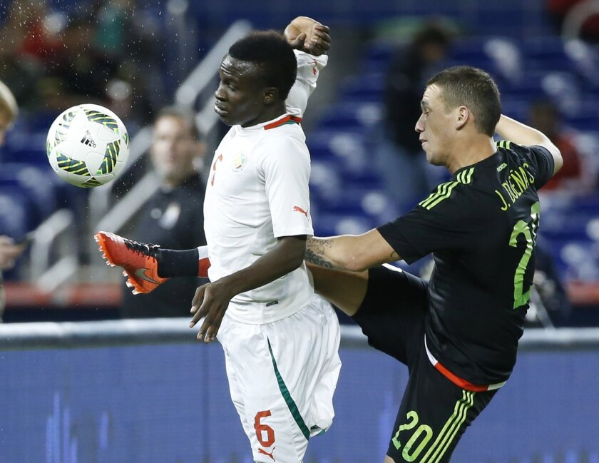 Mexico's Jesus Duenas (20) and Senegal's Elimane Oumar Cisse (6) battle for the ball during the first half of a soccer match at Marlins Park, Wednesday, Feb. 10, 2016, in Miami. (AP Photo/Wilfredo Lee)