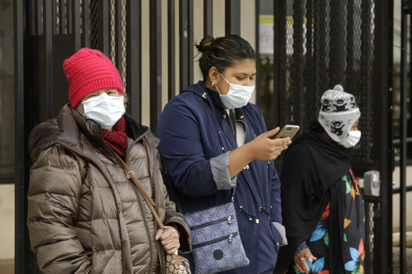 People wearing masks wait for a Lyft in downtown Los Angeles on Tuesday.