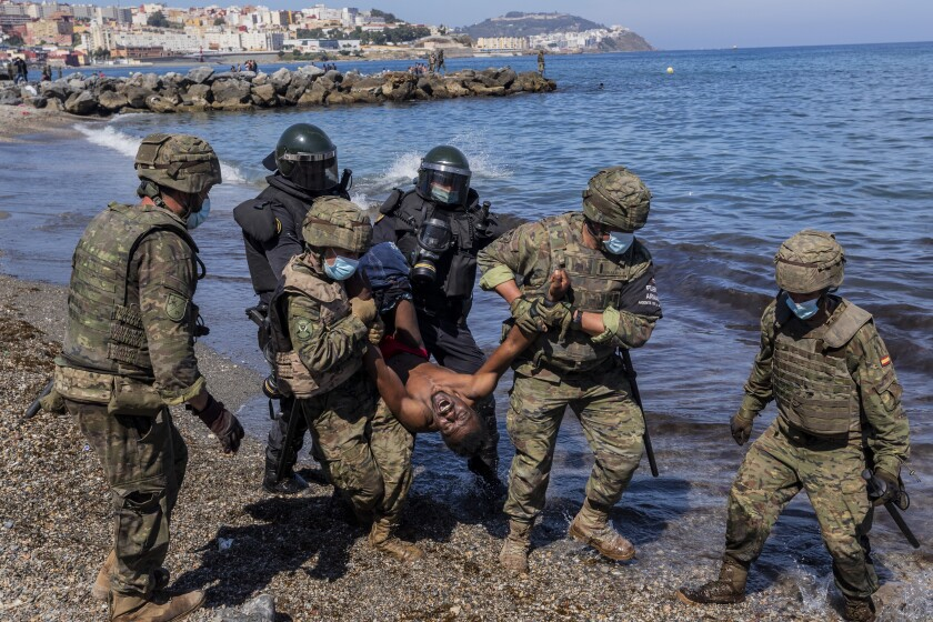 Spanish Army soldiers expel a migrant from the Spanish enclave of Ceuta, on Tuesday, May 18, 2021. About 8,000 people have streamed into the Spanish city of Ceuta from Morocco in the past two days in an unprecedented influx of migrants, most of them swimming across the border to reach the Spanish enclave in North Africa. (AP Photo/Bernat Armangue)