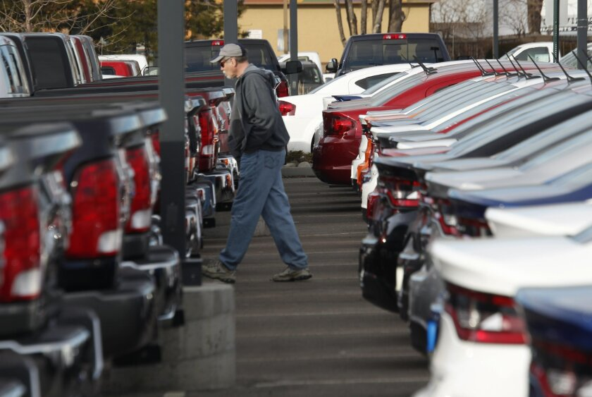 FILE - In this Sunday, Jan. 20, 2013, file photo, a buyer moves between rows of Ram pickup trucks and Dart sedans at a Dodge dealership in Littleton, Colo. Chrysler says its U.S. sales rose 8 percent in January 2014, as it posted strong growth despite the frigid weather that gripped much of the nation. (AP Photo/David Zalubowski, File)