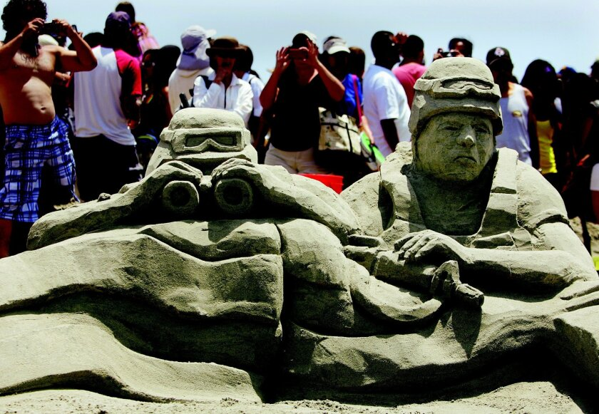 Crowds surround a sculpture thanking our military carved by the I.B. Posse at the 31st Annual US Open Sand Castle Competition on Sunday in Imperial Beach, California in 2011.