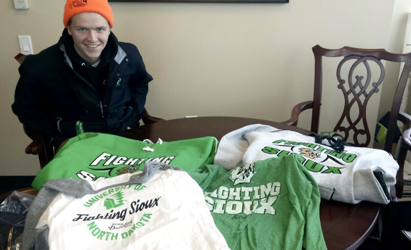 In this Feb. 9, 2016 photo provided by Marlys Lord Carlson, University of North Dakota freshman Nick Carlson smiles over his haul of UND Fighting Sioux gear that he bought at Ralph Engelstad Arena in Grand Forks, N.D. The merchandise is part of the Dacotah Legacy Collection that includes a limited