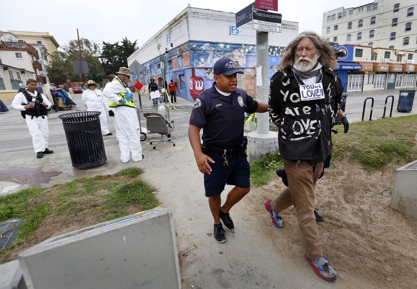 Homeless activist David Busch is led away by an LAPD officer during a 2015 sanitation sweep in Venice.