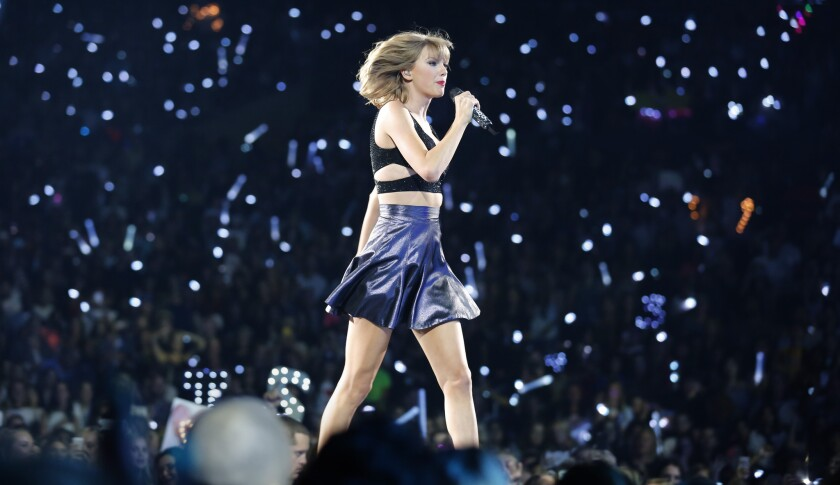 Taylor Swift on stage at Staples Center in Los Angeles on Aug. 21, 2015. Lights in the background are from cellphones and lighted wristbands Swift supplied to every member of the audience to more fully integrate fans into her concert.