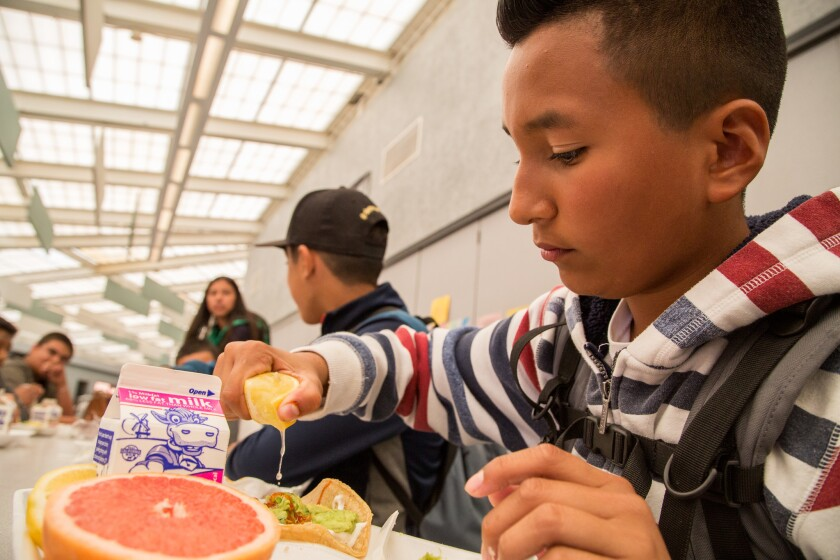 """8th grader, Oscar Peña, squeezes lemon onto a grilled fish taco during """"California Thursdays,"""" at San Ysidro Middle School. March, 17 2016. Photo by David Hodges."""