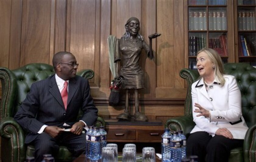 FILE - In this Saturday, Aug. 4, 2012 file photo, U.S. Secretary of State Hillary Rodham Clinton, right, meets Chief Justice Willy Mutunga at the Supreme Court of Kenya, in Nairobi, Kenya.  Mutunga is making an extraordinary public statement that he will not be cowed by threats and harassment ahead