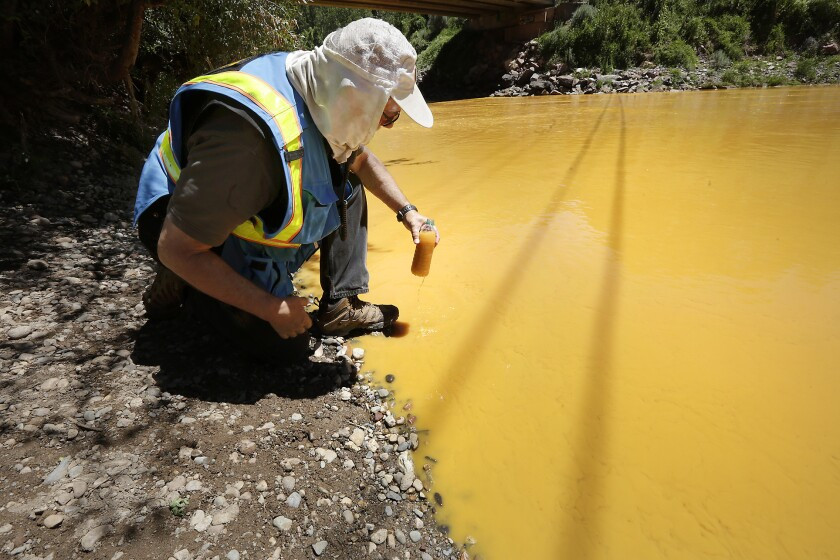 Dan Bender, with the La Plata County Sheriff's Office, takes a water sample from the Animas River near Durango, Colo., on Aug. 6, 2015, after the accidental release of an estimated 3 million gallons of waste from the Gold King Mine. Federal officials fear that at least six of the sites examined by The Associated Press could have blowouts like the one at Gold King.