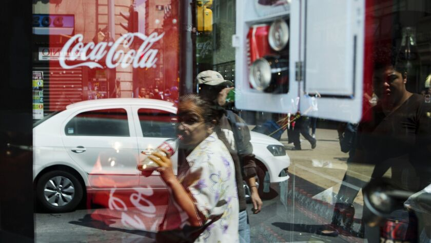 FILE - In this Oct. 9, 2014 file photo, a woman is reflected in a Coca-Cola store window display as