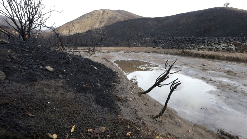Mud and debris has washed down normally-dry Solstice Creek in an area burned by the Woolsey Fire in