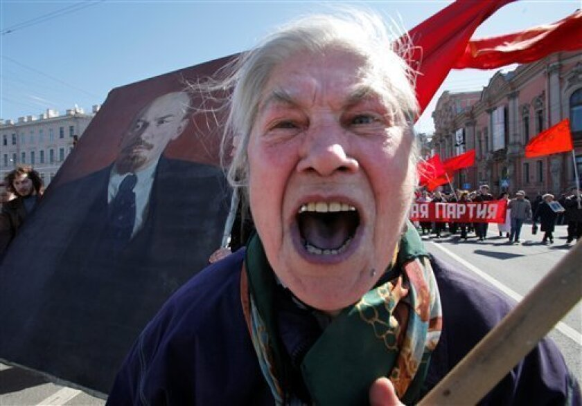 Yelena Saratova shouts as she and other Communist supporters march to mark May Day in downtown St. Petersburg, Russia, Friday, May 1, 2009, with a portrait of the Soviet founder Vladimir Lenin at left. During the Soviet era, May 1 was a major celebration of worker solidarity, Soviet might and the advent of spring. After the Soviet collapse, it provided an opportunity for Communists and others angry over the switch to lopsided capitalism to vent criticism. (AP Photo/Dmitry Lovetsky)