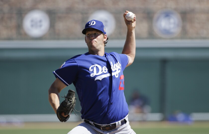 Los Angeles Dodgers starting pitcher Clayton Kershaw throws against the Chicago White Sox during a spring training baseball game.