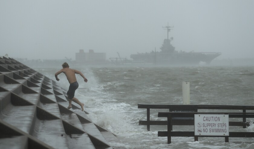 A beachgoer jumps to higher ground as Hurricane Hanna begins to make landfall Saturday in Corpus Christi, Texas.