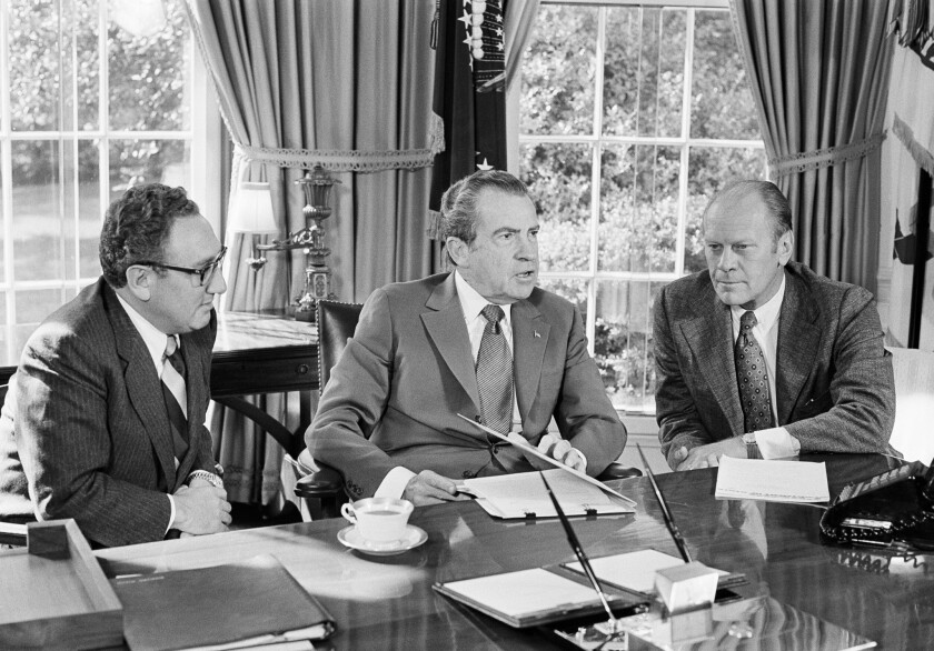 Gerald R. Ford, right, then-vice presidential nominee, listens as President Richard Nixon, accompanied by Secretary of State Henry Kissinger, speaks in the Oval Office of the White House on Oct. 13, 1973.