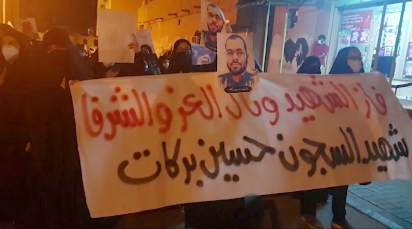 """In this image made from video provided by the Bahrain Institute for Rights and Democracy, demonstrators march to protest the death of a prisoner in Diah, Bahrain, Wednesday, June 9, 2021. Hundreds on Wednesday held a rare protest in Bahrain over the death of a vaccinated prisoner from the coronavirus held by the island kingdom. The banner in Arabic reads: """"The liberated and honorable martyr has prevailed, the martyr prisoner Husain Barakat."""" (Bahrain Institute for Rights and Democracy via AP)"""