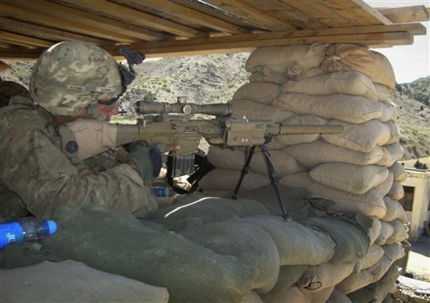 A U.S. soldier with the 1st battalion 3rd brigade and 1st infantry division monitors the area through the scope of his weapon at a check post of a joint U.S. and Afghan security forces base in Musa khel, district of Khost province southeast of Kabul, Afghanistan on Saturday, April 30, 2011. (AP Photo/Nishanuddin Khan)