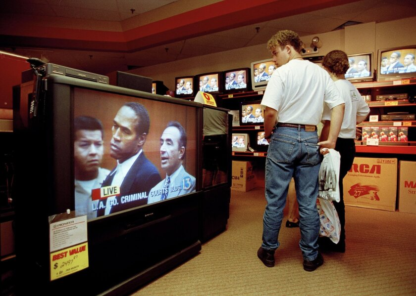 """FILE - In this June 20, 1994 file photo, mall shoppers in Tampa, Fla., watch banks of televisions in an electronics store as the arraignment of O.J. Simpson is televised from Los Angeles. The O.J. Simpson trial was labeled the """"Trial of the century"""" and a forerunner of today's interactive media. (AP Photo/Chris O'Meara, File)"""