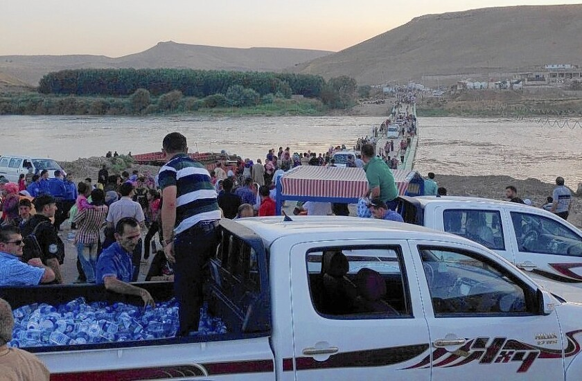 Iraqi Yazidis who fled Islamic militants several days ago cross the Tigris River from Syria into Iraq on Aug. 9, met by offerings of bottled water.