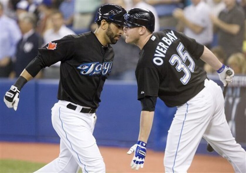 Toronto Blue Jays' Jose Bautista, left, celebrates his second inning home run with teammate Lyle Overbay during a baseball game in Toronto on Friday, June 4, 2010. (AP Photo/The Canadian Press, Darren Calabrese)