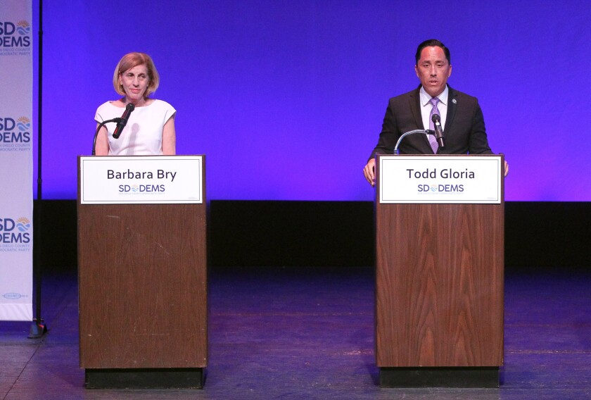 Candidates for San Diego mayor Barbara Bry and Todd Gloria stand onstage during a candidates forum in 2019.